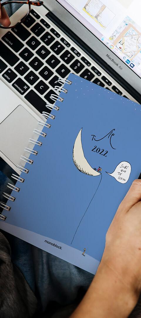 Una mujer sostiene una agenda anillada en sus manos, sobre una computadora portátil. La tapa de la agenda, fondo azul, es un cómic del humorista gráfico Tute.
