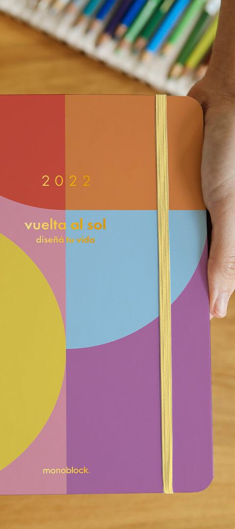 Una mano sosteniendo una agenda anillada Vuelta al Sol 2022, de colores vibrantes, con detalles metalizados, puntas redondeadas y elástico amarillo, sobre un fondo de madera y una caja de lápices de colores fuera de foco